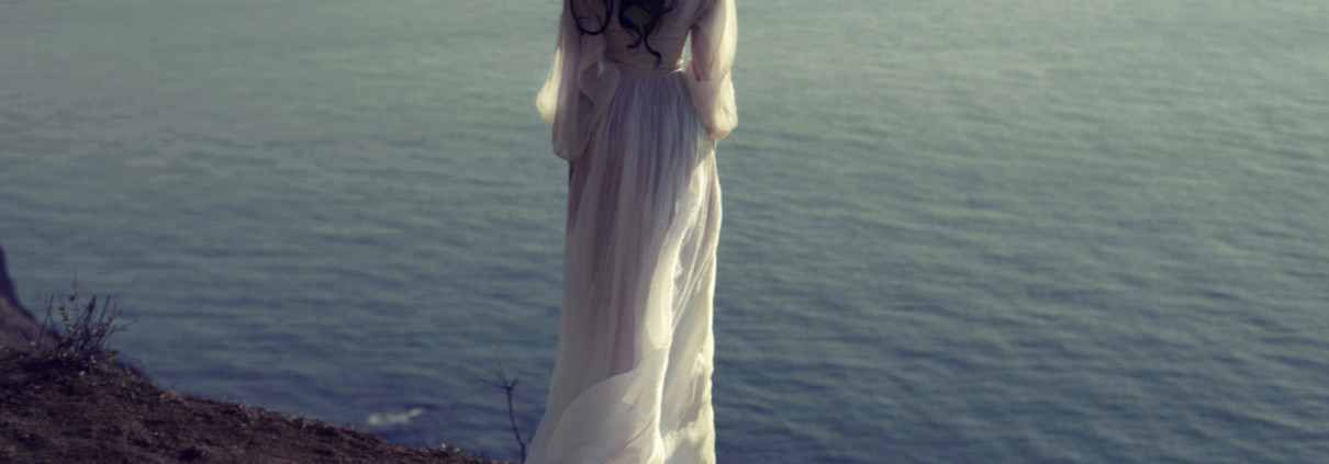girl in a long white dress on the beach